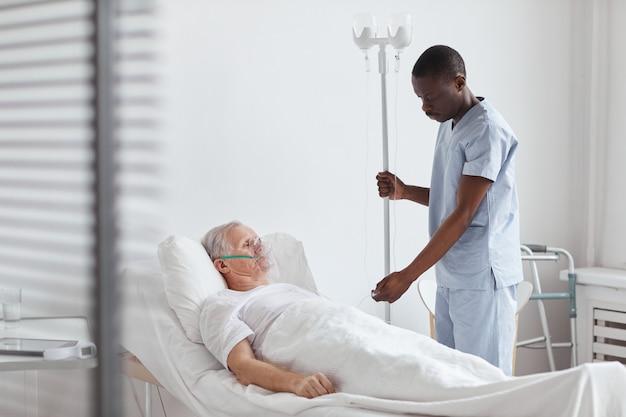 Porträt eines afroamerikanischen krankenpflegers, der einen iv-tropf einrichtet, während er einen älteren patienten im krankenhausbett behandelt, kopierraum