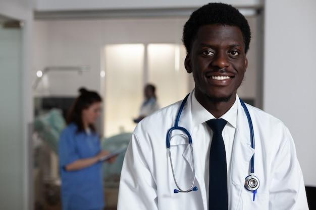 Porträt eines afroamerikanischen mannes, der am schreibtisch der krankenstation arbeitet?