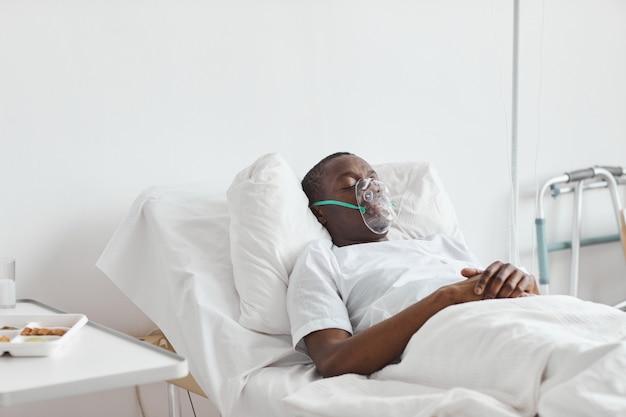 Porträt eines afroamerikanischen mannes, der auf einem krankenhausbett mit sauerstoffmaske im weißen raum schläft, kopierraum