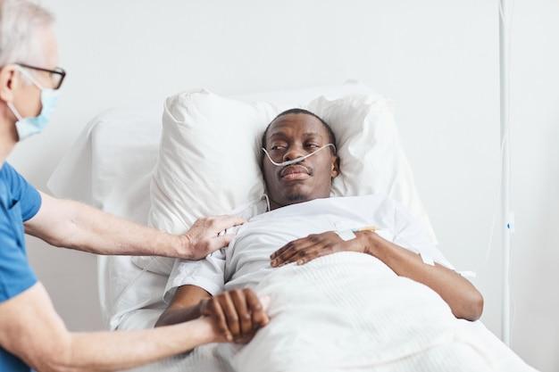 Porträt eines afroamerikanischen mannes, der im krankenhausbett liegt, mit einem leitenden arzt, der ihn tröstet, kopienraum