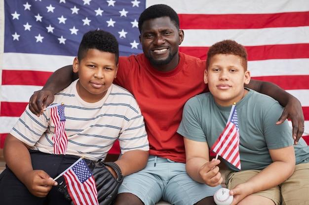 Porträt eines afroamerikanischen mannes, der söhne im teenageralter gegen die nationale amerikanische flagge umarmt
