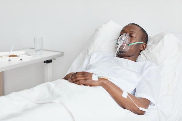 Porträt eines afroamerikanischen mannes im krankenhausbett mit sauerstoffmaske und iv-tropf, kopierraum