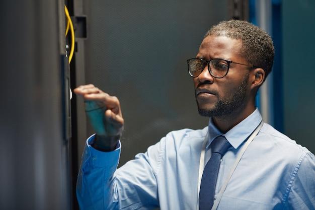 Porträt eines afroamerikanischen netzwerkingenieurs, der in servern einrichtet, während er mit einem supercomputer im rechenzentrum arbeitet, platz kopieren