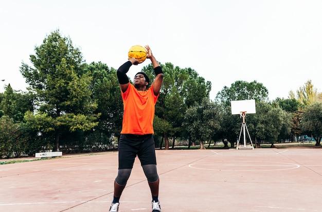 Porträt eines afroamerikanischen schwarzen jungen, der basketball auf einem städtischen platz spielt. mit einem orangefarbenen t-shirt bekleidet.