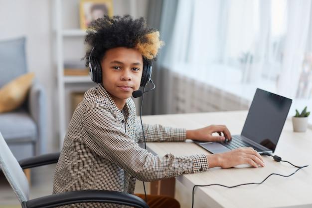 Porträt eines afroamerikanischen teenagers, der ein headset trägt und die kamera anschaut, während er zu hause einen laptop verwendet, ein junges gamer- oder blogger-konzept, kopierraum