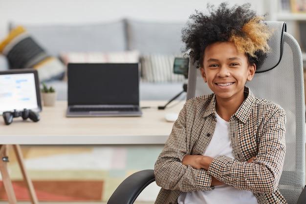Porträt eines afroamerikanischen teenagers, der in die kamera lächelt, während er im stuhl gegen eine spielstation mit laptop und video-streaming-geräten sitzt, kopierraum