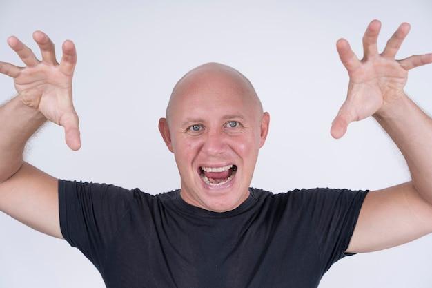 Porträt eines aggressiven glatzköpfigen mannes, drinnen, aus nächster nähe. nahaufnahmetrieb des kaukasischen kahlen mannes, der gerade kamera betrachtet. menschen und lifestyle-konzept