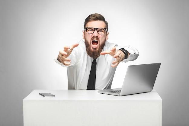 Porträt eines aggressiven, wütenden jungen geschäftsmannes in weißem hemd und schwarzer krawatte beschuldigen sie im büro und haben schlechte laune, schreien und wollen sie erwürgen. indoor, studioaufnahme, grauer hintergrund