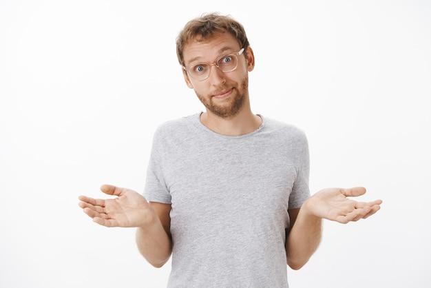 Porträt eines ahnungslosen und unbekümmerten, gut aussehenden erwachsenen mannes mit borsten in gläsern, die mit gespreizten händen die achseln zucken, ohne rücksicht auf ein schlechtes ergebnis, das sich sorglos anfühlt