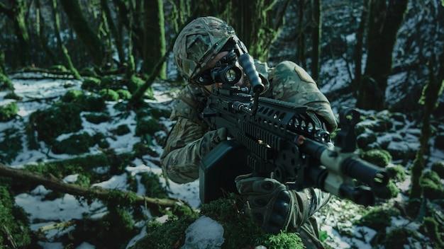 Porträt eines airsoft-spielers in professioneller ausrüstung im helm, der auf ein opfer mit einer waffe im wald abzielt. soldat mit waffen im krieg