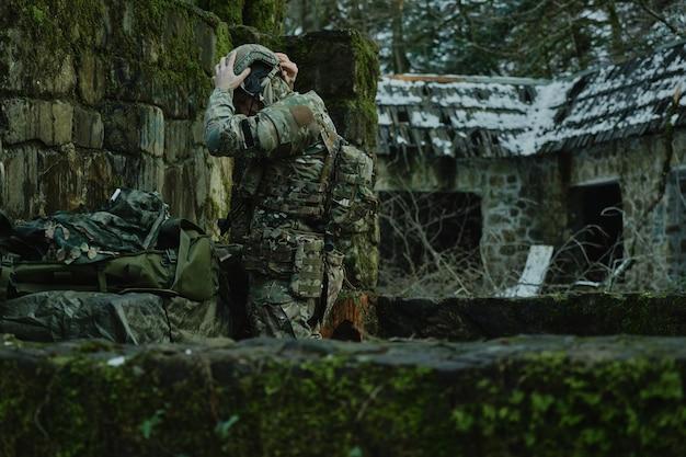 Porträt eines airsoft-spielers in professioneller ausrüstung mit maschinengewehr im wald. soldat mit waffen im krieg