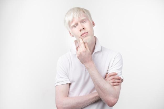 Porträt eines albinomannes in studio kleidete das t-shirt, das auf einem weißen hintergrund lokalisiert wurde. abnorme abweichungen. ungewöhnliches aussehen. hautanomalie