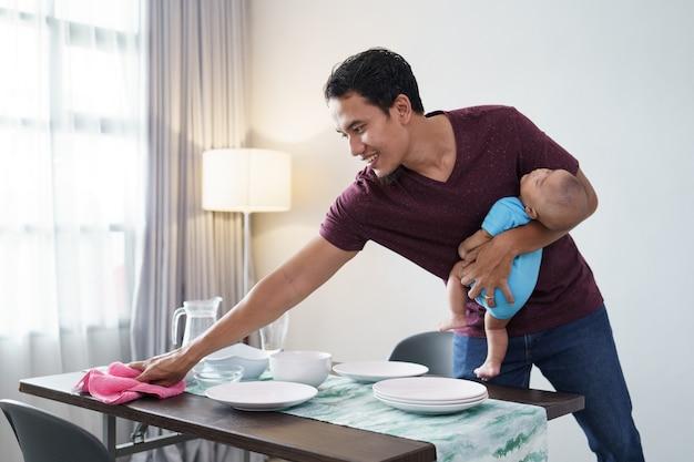 Porträt eines alleinerziehenden vaters, der hausarbeiten zu hause erledigt, während er sein baby trägt