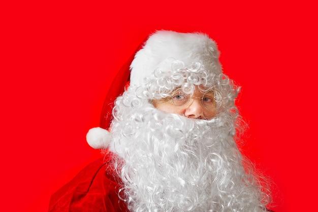 Porträt eines als weihnachtsmann verkleideten mannes auf rotem grund