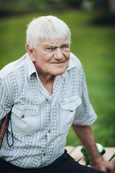 Porträt eines alten kaukasischen großvaters mit hellem haar im weißen hemd, das auf einer bank sitzt, lächelt und sein leben genießt