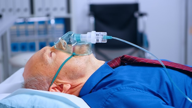 Porträt eines alten männlichen patienten mit sauerstoffmaske, der während der globalen gesundheitspandemie des coronavirus covid-19 auf dem krankenhausbett liegt. hilfe beim atmen gegen atemwegsinfektionen in einer modernen klinik bekommen