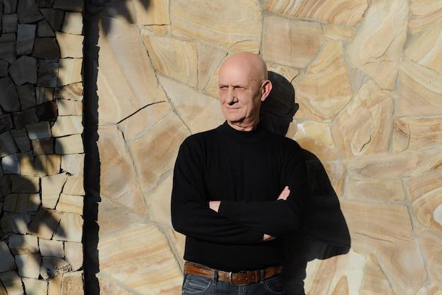 Porträt eines alten mannes auf dem hintergrund einer steinmauer Premium Fotos