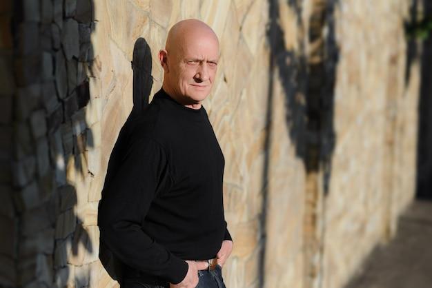 Porträt eines alten mannes auf dem hintergrund einer steinmauer