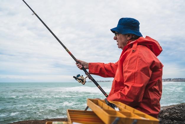 Porträt eines alten mannes, der im meer fischt. angelkonzept.