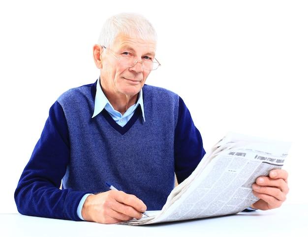 Porträt eines alten mannes, der kreuzworträtsel in der zeitung löst