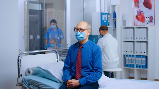 Porträt eines alten mannes mit maske beim arzttermin, der auf dem krankenhausbett sitzt und auf covid-19-ergebnisse wartet. medizinisches medizinsystem im gesundheitswesen während der globalen pandemie, handheld-zeitlupenaufnahme