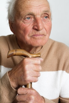 Porträt eines alten traurigen mannes, der seinen kopf auf den griff eines hölzernen stocks setzte.