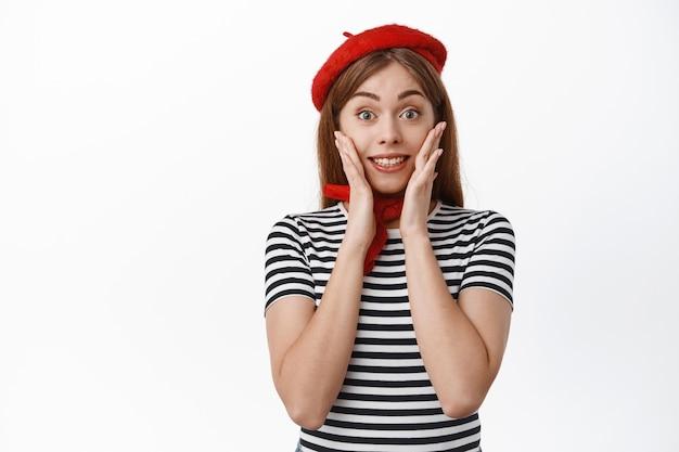 Porträt eines amüsierten mädchens in französischer baskenmütze, das die hände im gesicht hält, lächelt und aufgeregt auf das sonderangebot schaut, auf große ankündigung reagiert, weiße wand