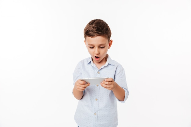 Porträt eines amüsierten niedlichen kleinen kindes, das spiele spielt