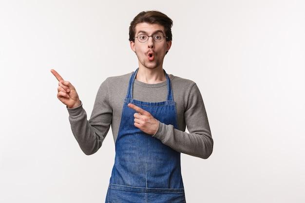 Porträt eines amüsierten und überraschten aufgeregten männlichen angestellten, der mit einem kollegen über erstaunliche technische fähigkeiten des neuen barista spricht, den finger nach links zeigt und die lippen faltet, sagt wow erstaunt,