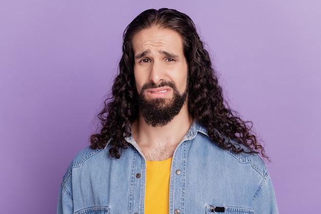 Porträt eines angewiderten grimassierenden, unruhigen kerls, der die kamera auf lila hintergrund verärgert sieht