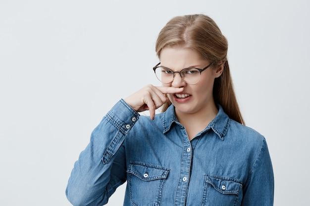 Porträt eines angewiderten mädchens, das nase drückt. blonde frau, die nase hält, die etwas stinkendes riecht. studentin, die brille und blaues hemd trägt, das mit ekel schaut. gesichtsausdruck und reaktion.