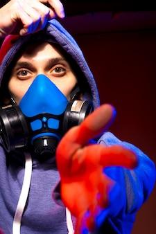 Porträt eines anonymen mannes, hacker, der neonmaske über dunklem hintergrund trägt. selektiver fokus eines bi-rassischen cyberpunk-spielers, der waffen in der nähe von neonlicht hält
