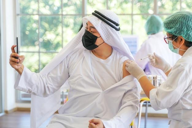 Porträt eines arabischen muslimischen mannes selfie per telefon nach erhalt des covid-impfstoffs, um immunität zu erhalten