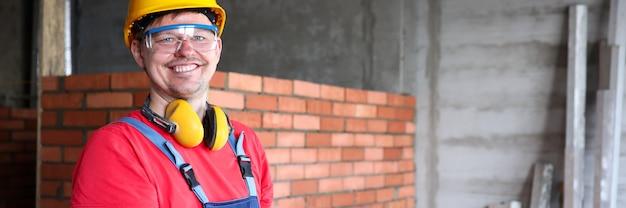 Porträt eines arbeitenden bauherrn oder ingenieurs, der informationen in die zwischenablage schreibt. mann, der schutzhelm, brille und handschuhe trägt.