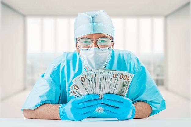 Porträt eines arztes, der hundert dollarnoten hält. er schaut in die kamera und lächelt