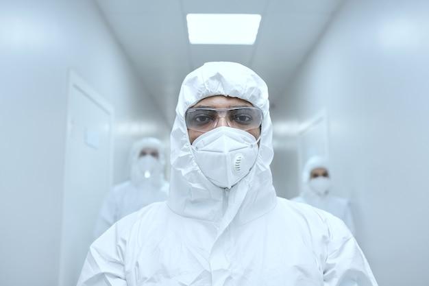 Porträt eines arztes in schutzbrille und maske, der während der arbeit während der pandemie im krankenhaus in die kamera schaut