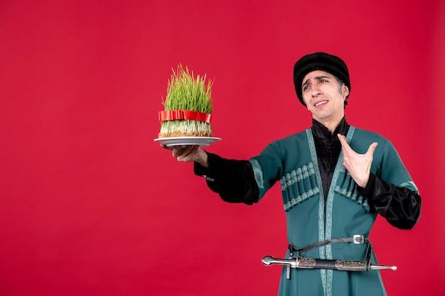 Porträt eines aserbaidschanischen mannes in traditioneller tracht, der auf rotem tänzer novruz feiertagsfrühling semeni gibt