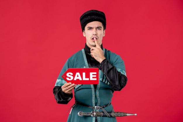 Porträt eines aserbaidschanischen mannes in traditioneller tracht, der das typenschild des verkaufs hält?