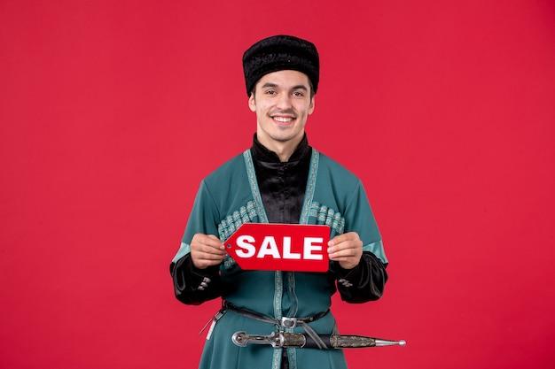 Porträt eines aserbaidschanischen mannes in traditioneller tracht, der das typenschild rot hält