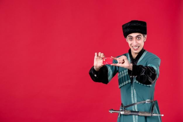 Porträt eines aserbaidschanischen mannes in traditioneller tracht, der eine kreditkarte hält, schoss rote ethnische novruz-frühlingsgeldfarbe