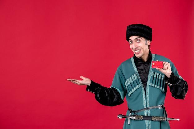 Porträt eines aserbaidschanischen mannes in traditioneller tracht, der kreditkarte auf rotem geldfarbfrühling ethnischen novruz hält