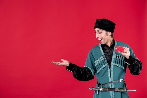 Porträt eines aserbaidschanischen mannes in traditioneller tracht, der kreditkarte auf rotem geldfrühlingsfarbe ethnischen novruz hält