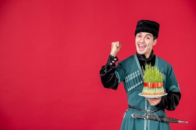Porträt eines aserbaidschanischen mannes in traditioneller tracht, der semeni-studioaufnahme auf roter novruz-frühlingskonzept-performerfarbe hält