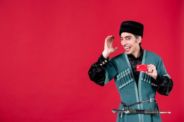 Porträt eines aserbaidschanischen mannes in traditioneller tracht mit kreditkarte studioaufnahme rotes frühlingsgeld ethnische novruz-farbe