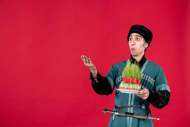 Porträt eines aserbaidschanischen mannes in traditioneller tracht mit semeni auf rotem tänzer ethnischer novruz-ferienfrühling