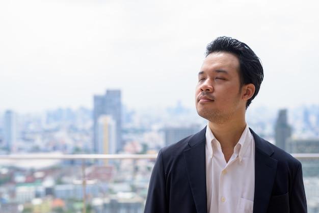 Porträt eines asiatischen geschäftsmannes, der anzug auf dem dach in der stadt trägt und sich mit geschlossenen augen entspannt