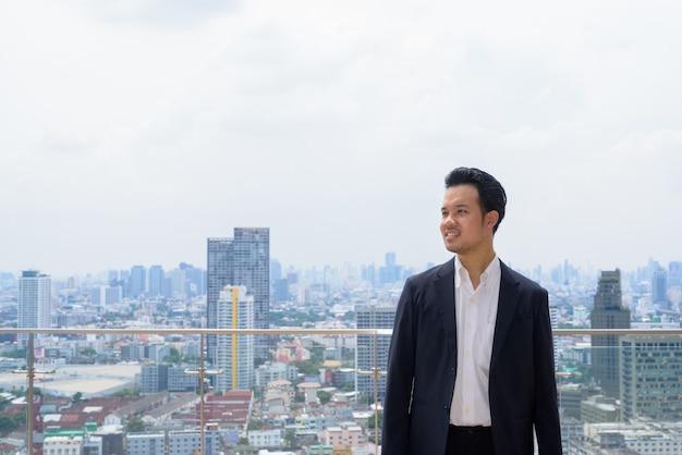 Porträt eines asiatischen geschäftsmannes, der anzug auf dem dach in der stadt trägt, während er denkt