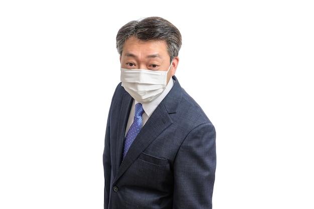 Porträt eines asiatischen geschäftsmannes mittleren alters, der eine weiße gesichtsmaske trägt.