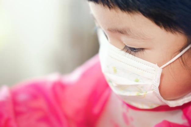 Porträt eines asiatischen mädchens mit hygienischer gesichtsmaske. konzepthintergrund für heimisolierung, gesundheitswesen und medica.