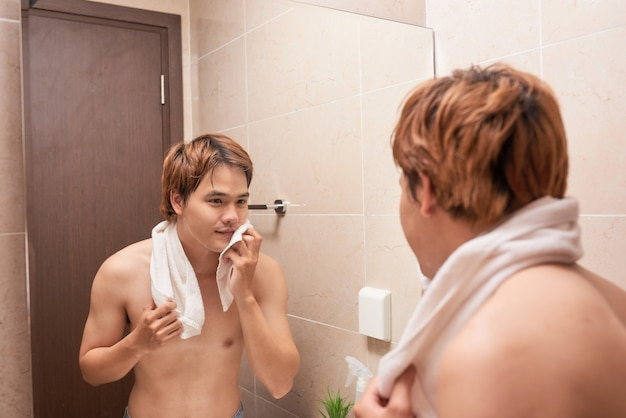 Porträt eines asiatischen mannes, der sich im badezimmer wäscht